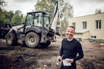 Man with plan of working in his hand is as a customer  on the construction site smiles and the modern excavator that performs excavation work on the construction site during reconstruction place