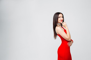 Studio portrait of beautiful sexy  woman with long brunette hair wearing bright red dress and make up, embracing herself holding hand at lips over white background. Copyspace.