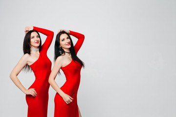 Two sexy and beautiful sisters twins in red dresses posing, looking at camera holding hands up. Pretty dancing ladies with long hair. Fashionable and stylish girls. Shopping, fashion, party.