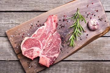 Raw beef steak T bone with ingredient