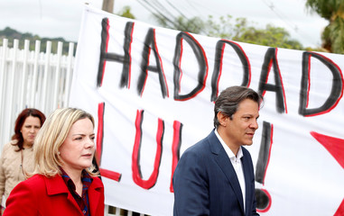 Brazil's Workers Party presidential candidate Fernando Haddad and Senator Gleisi Hoffmann leave the Federal Police headquarters, where Brazilian former President Luiz Inacio Lula da Silva is imprisoned, after visiting him in Curitiba