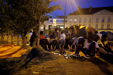 Migrants pray near tents in the downtown of Nantes