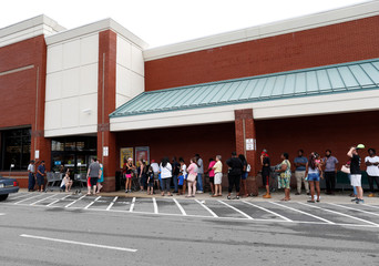 People wait in line to enter a grocery store after Tropical Storm Florence past through in Whiteville