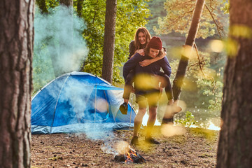 Happy couple of hikers having fun near a campfire at camp in the forest.