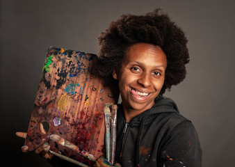 happy black woman holding a palette and paintbrushes on a gray background