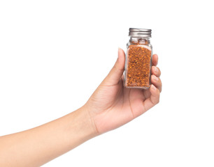 hand holding bottle of cayenne pepper isolated on white background