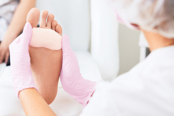 Patient on medical pedicure procedure visiting podiatrist.Podologic polymer gel plates.Protecting the skin ulceration.Bedsore prevention.Foot treatment in SPA salon.Podiatry clinic.