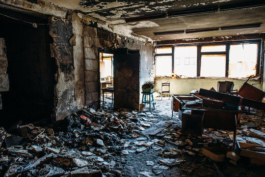 Burnt house interior. Burned room in industrial building, charred furniture and damaged apartment after fire