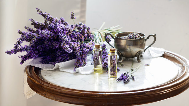 lavender oil bottles,  natural herb cosmetic consept with lavender flowers flatlay on stone background