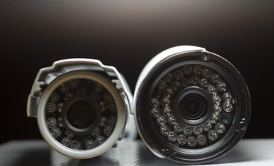 Surveillance cameras for sale photographed on a black background