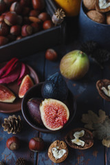 Fresh organic figs, nuts and autumn leaves on wooden board and dark stone table. Healthy lifestyle, seasonal fruit, sweet dessert, selective focus