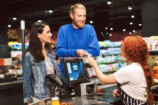 Young cheerful couple standing near cashier desk while happily giving credit card to teller in modern supermarket