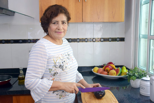mature woman cutting vegetables in kitchen
