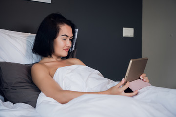 Portrait of happy young Caucasian woman sitting in bed, using digital tablet and smiling