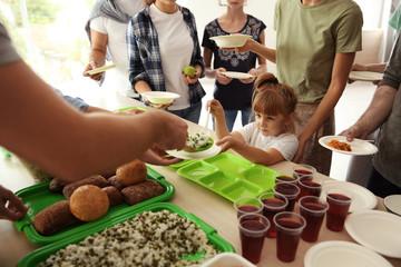 Volunteers serving food for poor people indoors