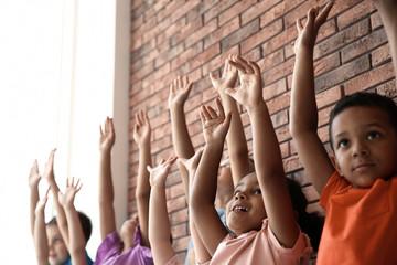 Little children raising hands together indoors. Unity concept