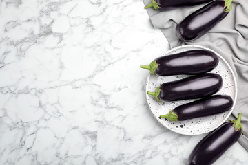 Raw ripe eggplants on marble background, top view