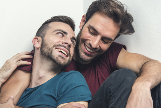 Happy gay couple embraced, joking and having fun in an intimate hug