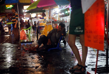 A street vendor sleeps as he sells souvenirs in Khaosan Road in Bangkok