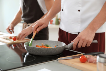 Male chef cooking vegetables on electric stove, closeup