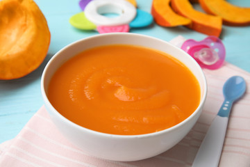 Bowl of healthy baby food on wooden table