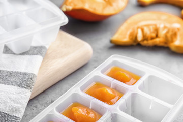 Ice cube tray with healthy baby food on gray table