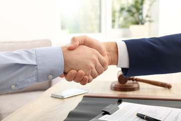Lawyer handshaking with client over table in office, closeup