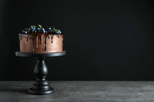 Fresh delicious homemade chocolate cake with berries on table against dark background. Space for text