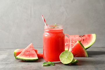 Summer watermelon drink in mason jar and sliced fruits on table