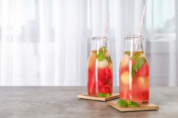 Bottles with tasty watermelon and melon ball drink on table. Space for text