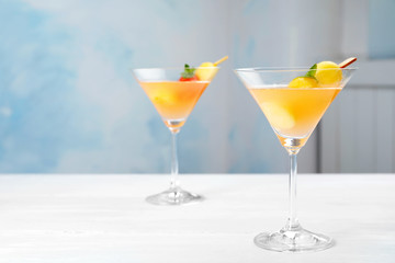 Glasses with tasty melon ball drink on table. Background with space for text
