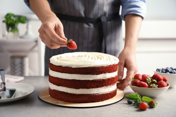 Woman decorating delicious homemade red velvet cake with strawberry at table