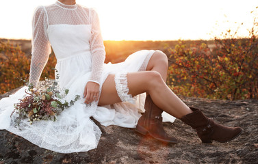 Beautiful bride with field bouquet sitting on rock at sunset, closeup