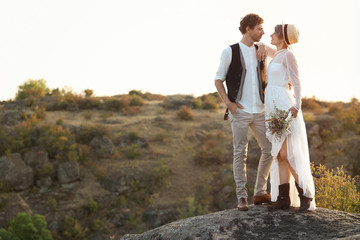 Happy newlyweds with beautiful field bouquet standing on rock outdoors