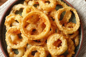 Homemade crunchy fried onion rings on plate, top view