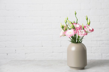 Beautiful flowers in vase and space for text on blurred background. Element of interior design