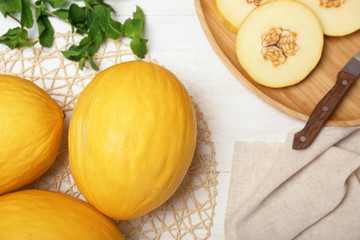 Flat lay composition with sliced ripe melons on wooden background