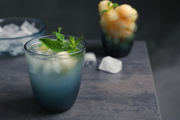 Glass with tasty melon ball drink on table against dark background. Space for text