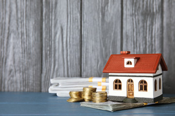 House model with money and space for text against wooden background
