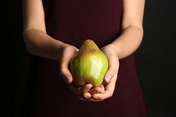 Woman holding ripe pear on black background, closeup