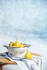 Colander with pears on table against color background. Space for text