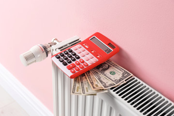 Heating radiator with calculator and money on color wall