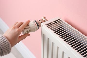 Woman adjusting heating radiator near color wall