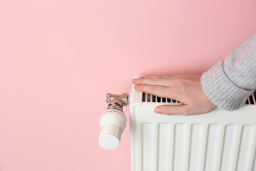 Woman warming hand on heating radiator against color background
