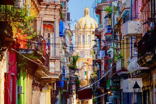 Colorful street in Old Havana with the Presidential Palace on the background