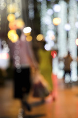 Blurry background image of defocused outdoor Christmas decorations with colorful lights and people in busy city street at night