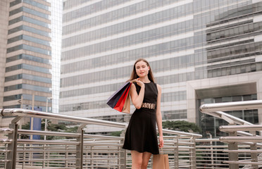 Portrait of beautiful female in black dress smling and holding shopping bags in city,Lifestyle concept