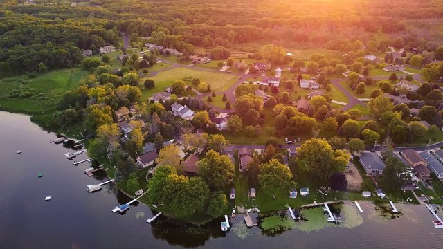 Aerial views of lake front and lakefront homes during a summer sunset.