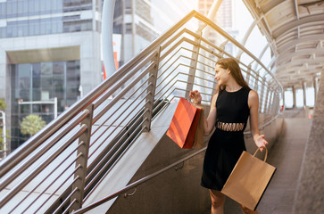 Young cheerful lady smling and holding shopping bags in mall,Happy female walking out from department store