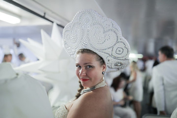 A woman poses on the ferry to Diner En Blanc, a secret pop up dinner, held this year on Governors Island in New York